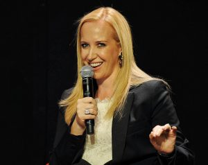 Alexandra Wilkis Wilson black background holding a microphone